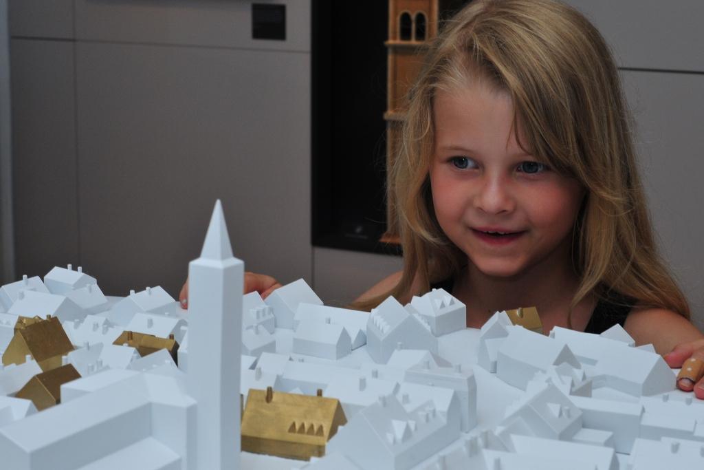 Ein Mädchen betrachtet staunend das Friedberger Stadtmodell im Museums